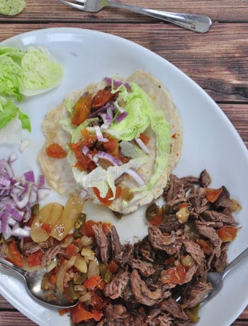 Overhead picture of tacos with some shredded beef and vegetables on