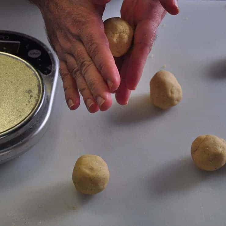 Four tortilla balls with one being rounded off in my hand for these homemade tortillas