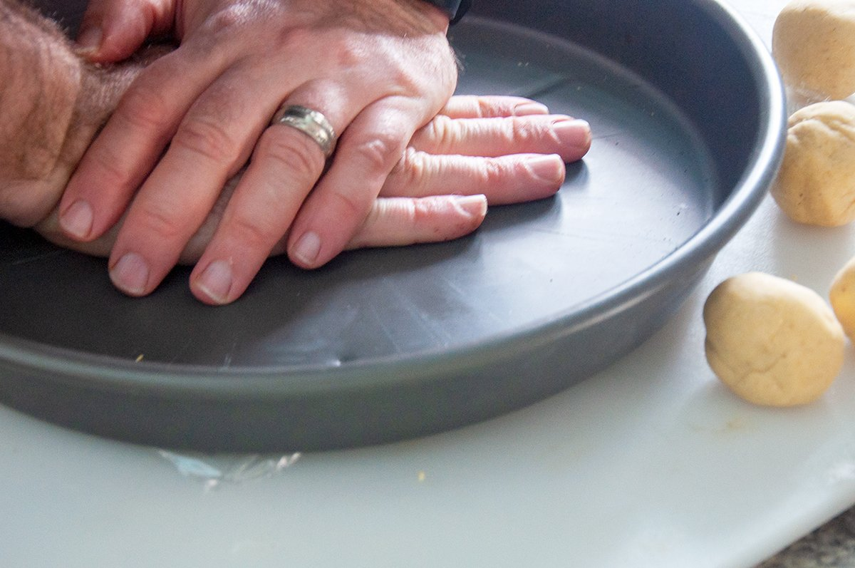 Two hands pressing down on a heavy dish for the purpose of flattening a tortilla.