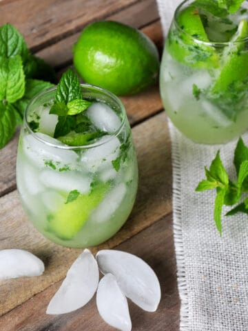 Mojito on a picnic table with mint, ice, and a whole lime.