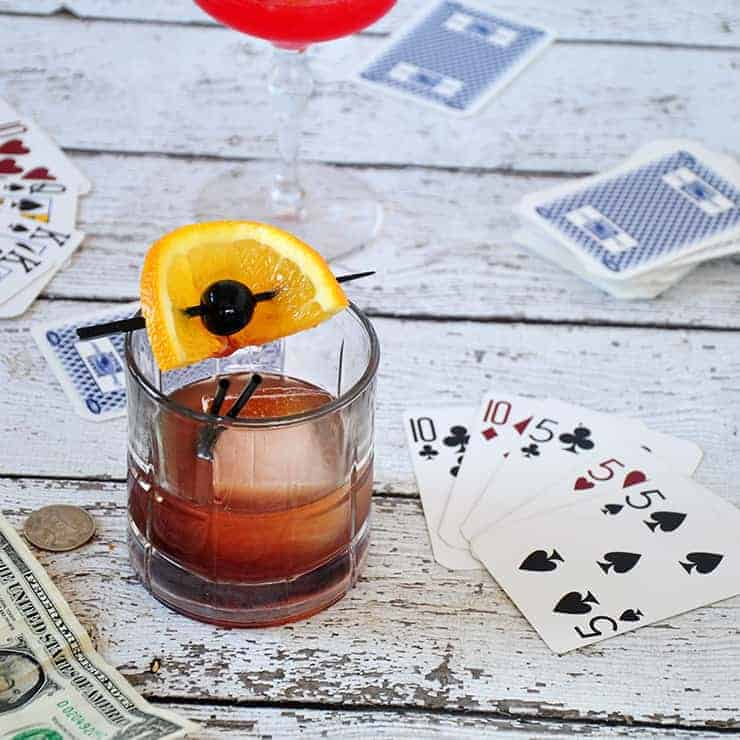 A picture of a mad men old fashioned on a park table with cards in the background