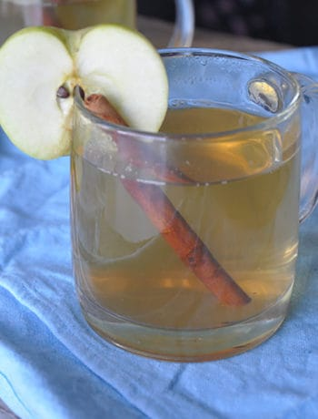 Apple Ginger Hot Toddy in irish coffee mug with cinnamon stick and apple slice.