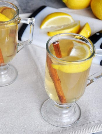 best hot toddy recipe. Hot toddy on a table with lemon, cinnamon, and a cutting board.