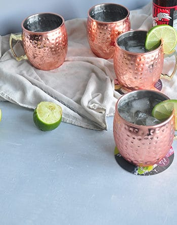 Moscow mule cocktails on a table with some spent limes - one on a cutting board