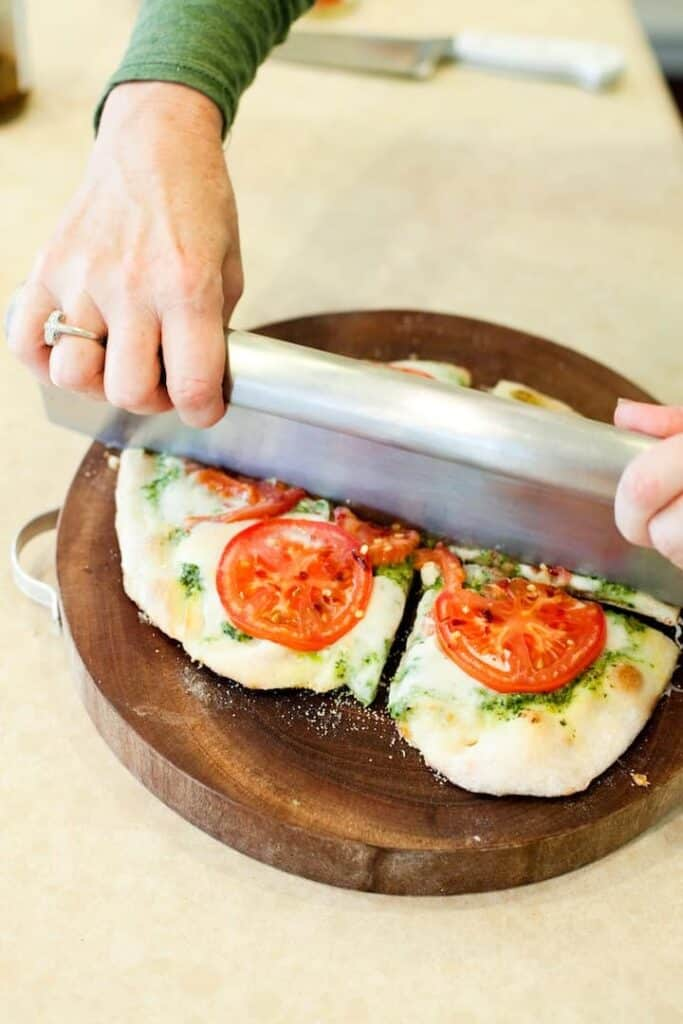 The organic Kitchen pesto and tomato pizza being cut in half