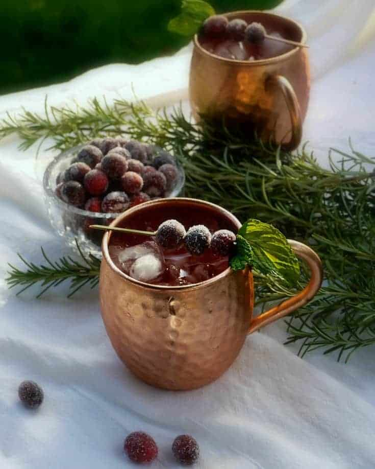 Spiced Mule in a copper cup with a some cranberries and green leafy spice on the table.