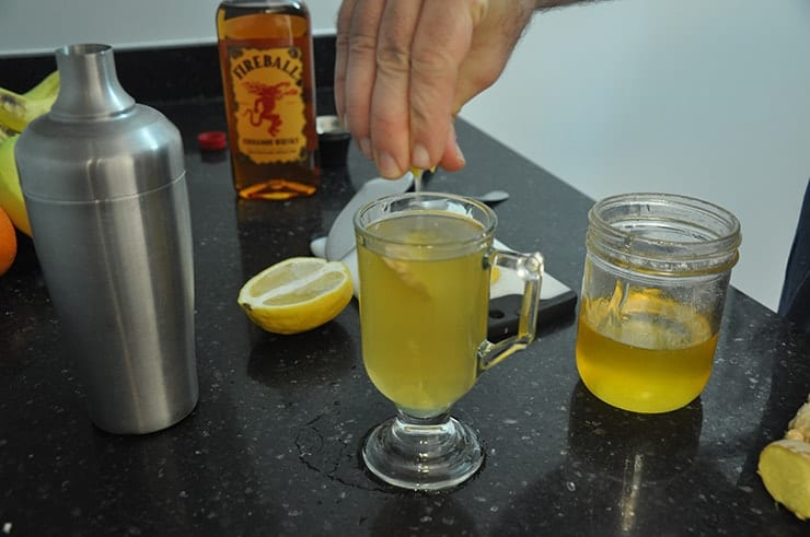 Squeezing lemon into completed 'Hot Toddy for a Cold' cocktail. Fireball, honey, and lemon in background.