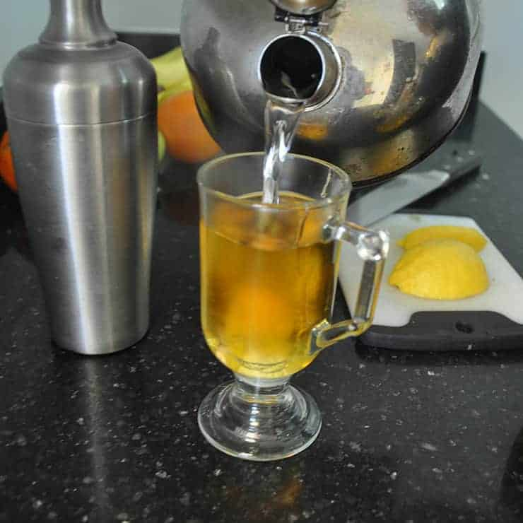 Pouring hot water into hot toddy on black countertop with shaker and lemon slices on the side