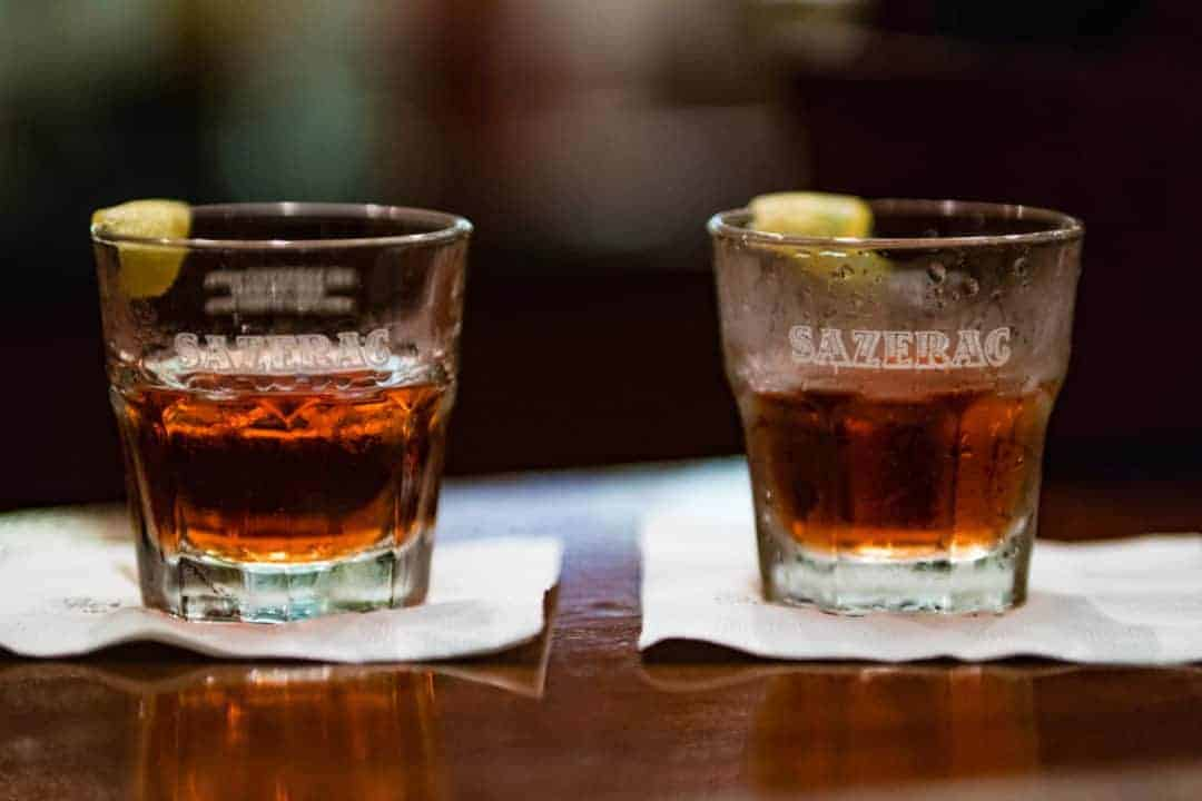 Picture of two Sazerac cocktails sitting on napkins that are on a brown, wooden table