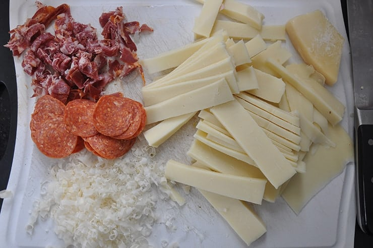 meats and cheeses laying on cutting board being prepped for Chicago Deep Dish