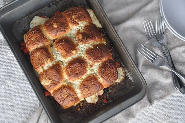 Finished Baked Pizza Sliders just waiting the be eaten and sitting in a pan next to some forks.