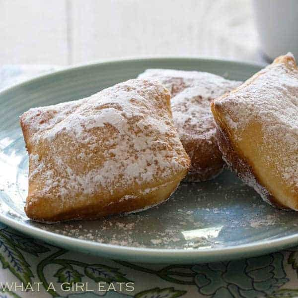 Three Beignets on a plate with powdered sugar on them