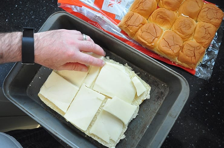Hawaiian buns layed out in pan with mozzarella cheese being layered on top