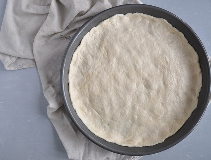 a picture of the dough in a deep dish pizza pan.