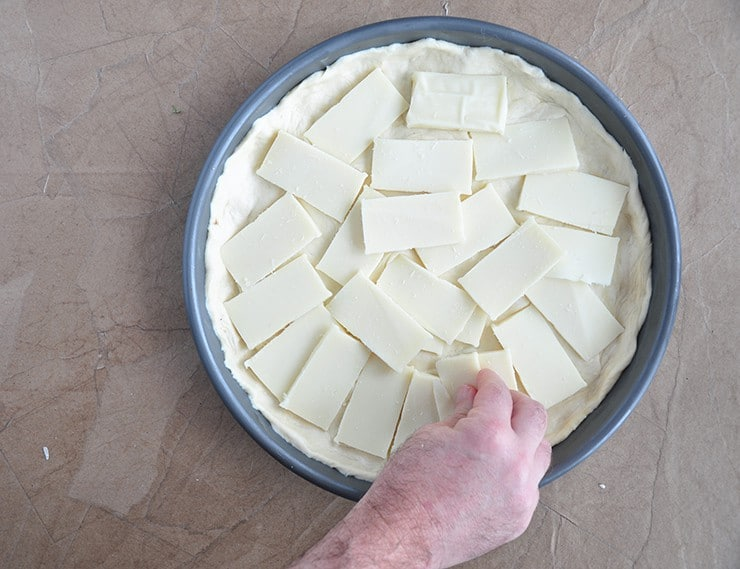 adding mozzarella to the deep dish dough in a deep dish pan