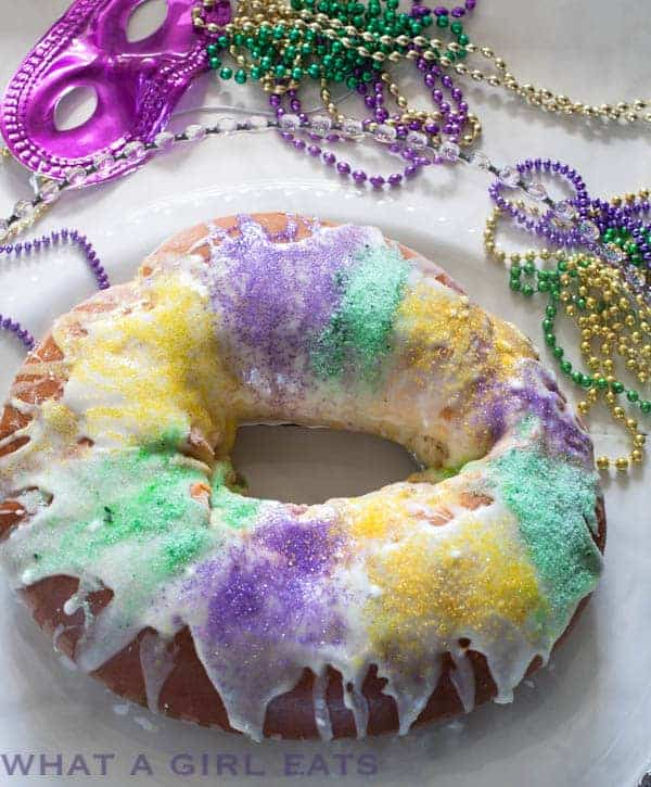 Image of New Orleans King Cake on a plate with Mardi Gras Beads