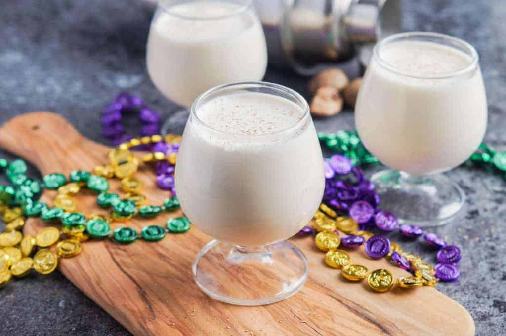 Three glasses of milk puch with beads in the background and sitting on a cutting board