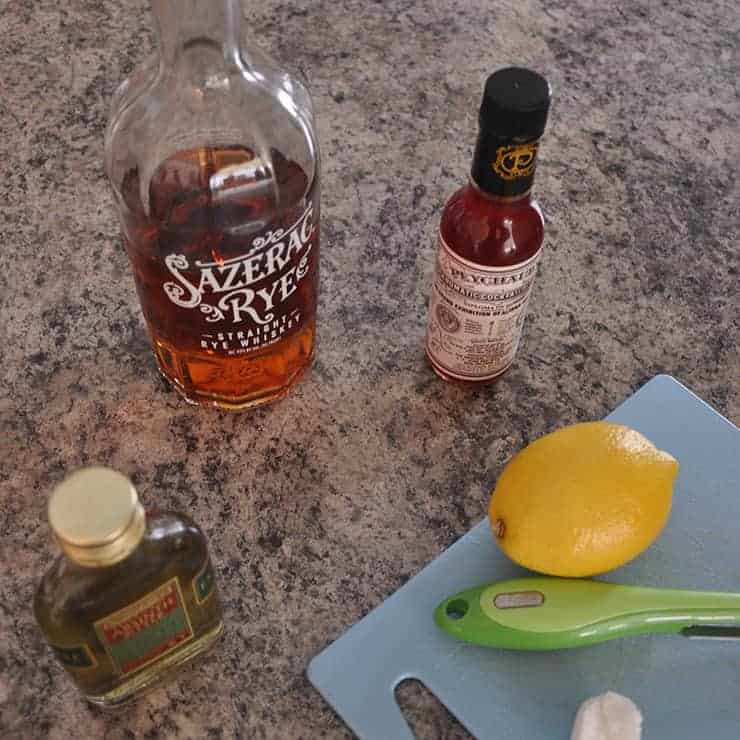 sazerac ingredients on a counter - whiskey, absinth, peychaud's bitters, lemon, sugar