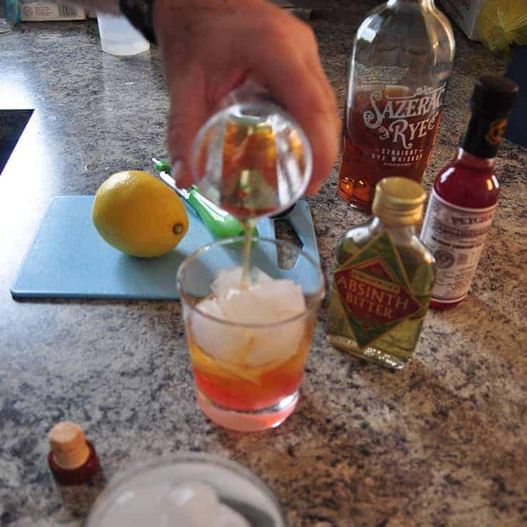 pouring rye whiskey into sazerac cocktail