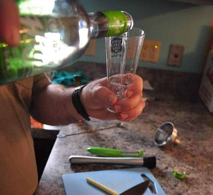 pouring hemp vodka into measuring vessel for cocktail