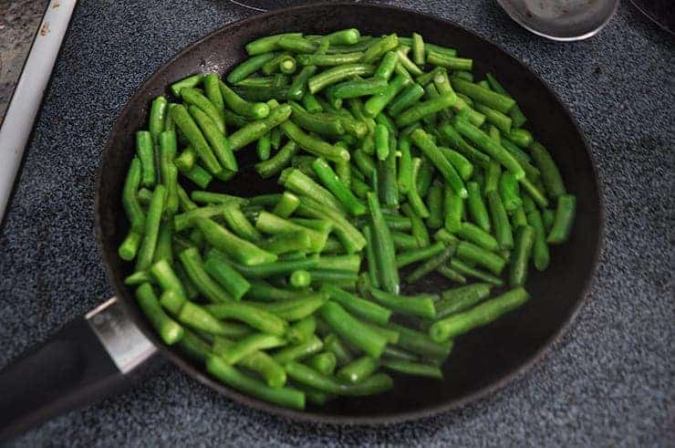 cooking some green beens in a pan