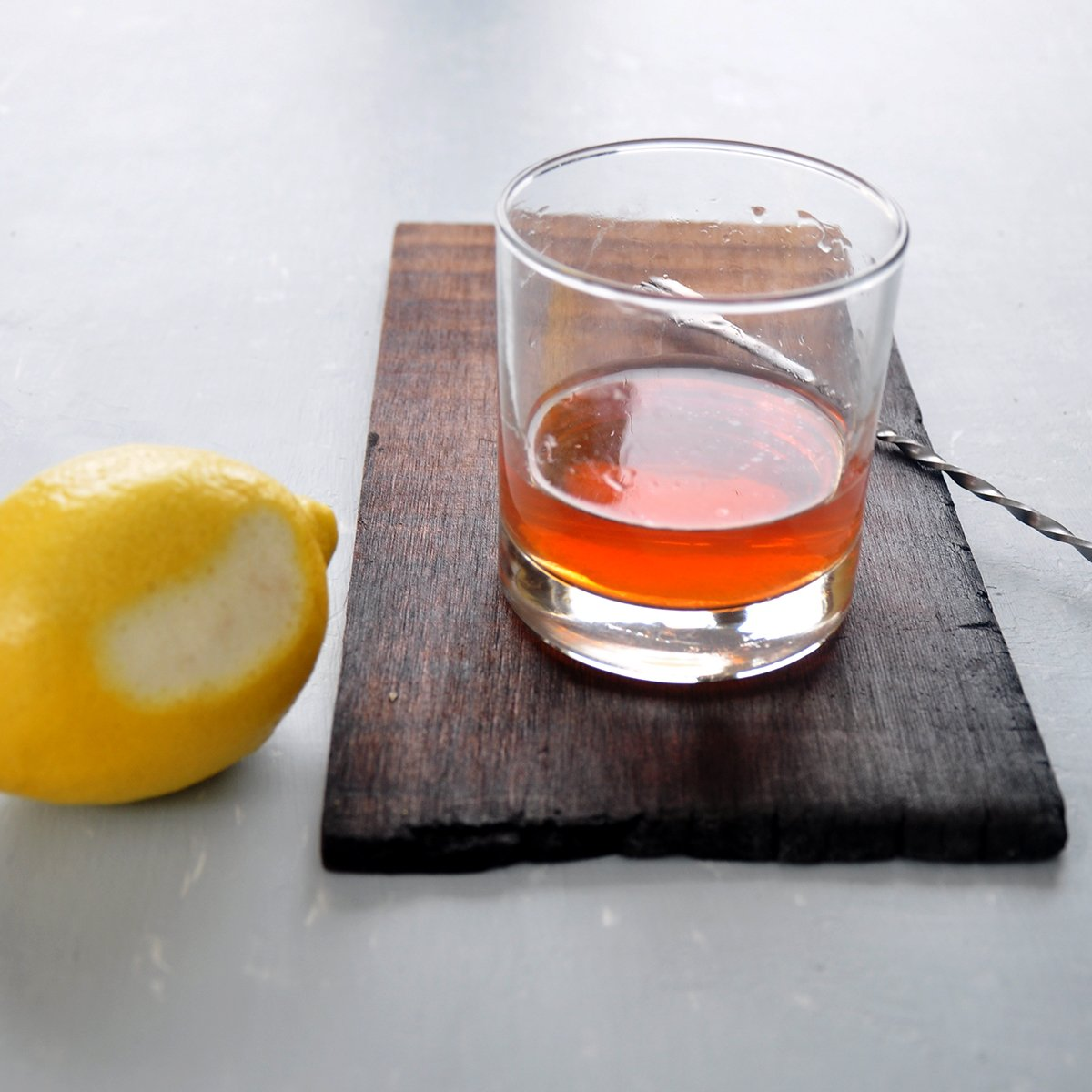 Sazerac on wood plank with lemon and mixing spoon