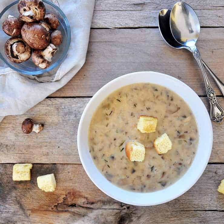 Overhead shot of cream of mushroom soup with croutons on top and mushrooms on the side. Two spoons on the side and all of it on old wood.