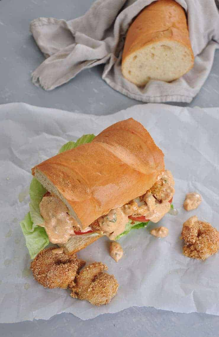 finished po' boy sandwich with remoulade sauce on it. French bread in background wrapped in cloth