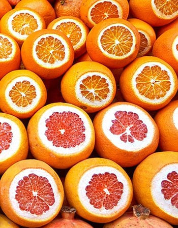 a bunch of grapefruits with the top third sliced off so you can look at the juicy insides of these citrus fruits