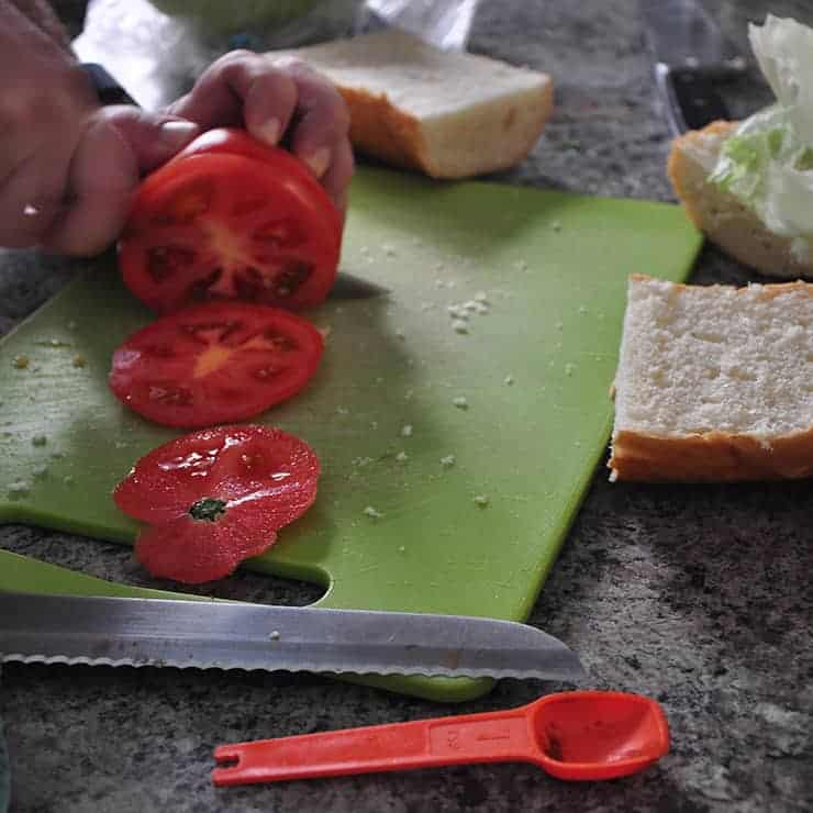 slicing french bread, tomatoes and lettuce for New Orleans Po' Boy sandwich