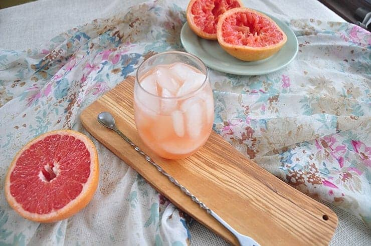 picture of a greyhound cocktail on a wood board with half a grapefruit and two juiced grapefruits