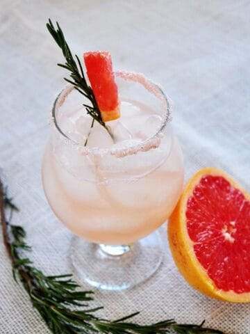 Rosemary infused Salty Dog on a mat. Half a grapefruit close by and a sprig of rosemary on the side