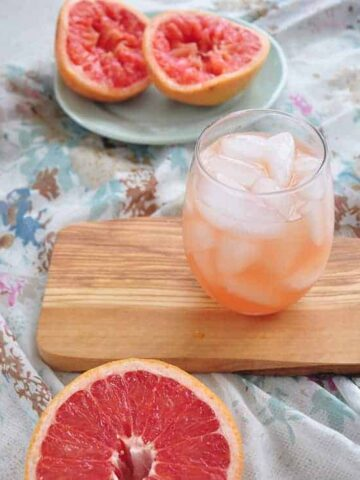greyhound cocktail recipe on wood platform with grapefruits