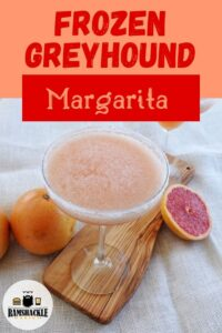 """""""Frozen Greyhound Margarita"""" with a drink in a margarita glass and fresh grapefruit in the background"""