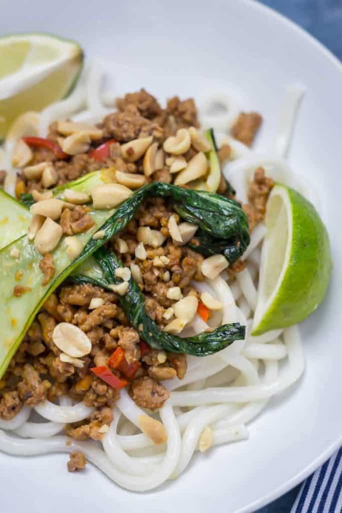 A plate of the noodles with peanuts on top ad a few limes on the side.