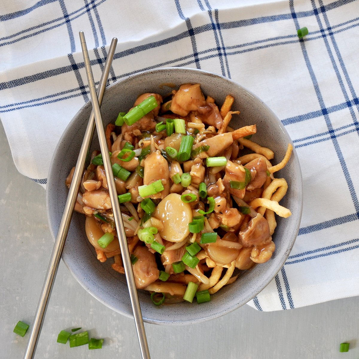 looking down on a bowl of crispy chicken chow mein in a grey bowl. There are chop sticks on top of the bowl, a plaid napkin is under the bowl. Green onions are on the table next to the bow.