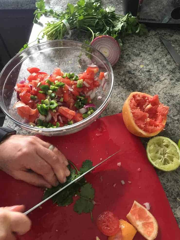 cutting cilantro on red cutting board with spent lime and grapefruit in the background, as well as a bowl of the fresh stuff