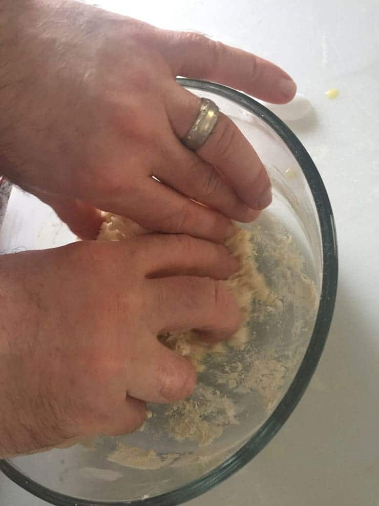 kneading dough in a glass bowl in preparation for making chow mein noodles