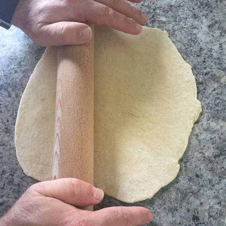 rolling out bread dough in order to make noodles with