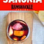 """""""Classic Red Sangria"""" with an overhead view of a glass of the cocktail on a cutting board and fruit in and out of the drink."""