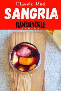 """Classic Red Sangria"" with an overhead view of a glass of the cocktail on a cutting board and fruit in and out of the drink."