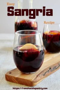 """Easy Sangria Recipe"" with a picture of two glasses of sangria on a board and a carafe in the background."