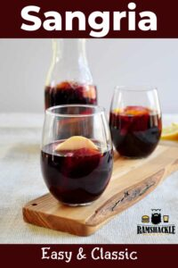 """Easy & Classic Sangria"" two glasses and a carafe of sangria on a cutting board."