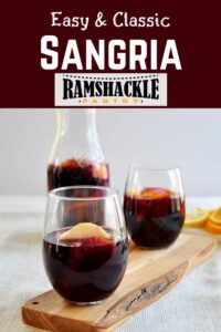 """Easy and Classic Sangria"" with two glasses of the red wine sangria and some fruit in the containers"
