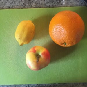 This is an orange, apple, and lemon on a cutting board