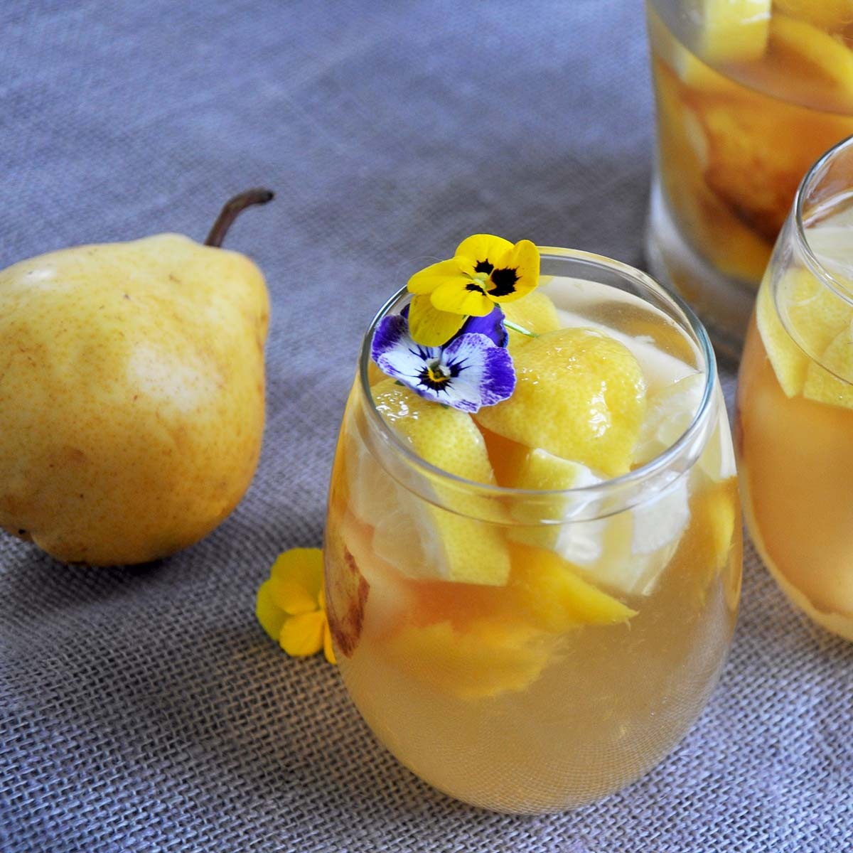 Glass of our best white sangria recipe with some viola flowers garnishing it with a pear and pitcher in the background