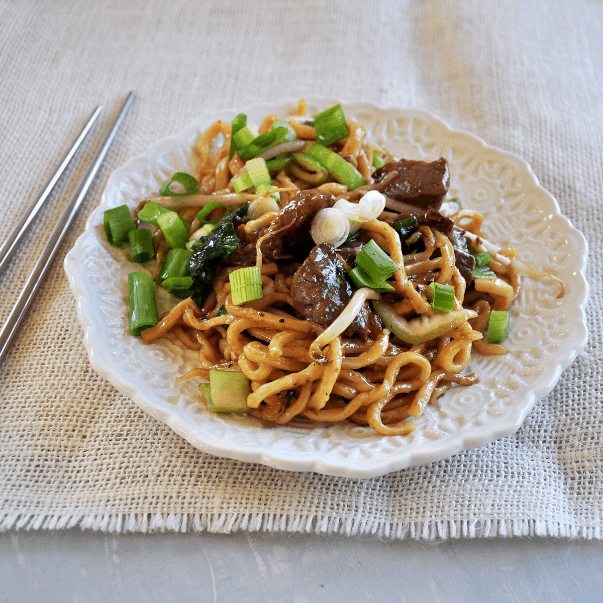 Beef Chow Mein from the side with chop sticks.