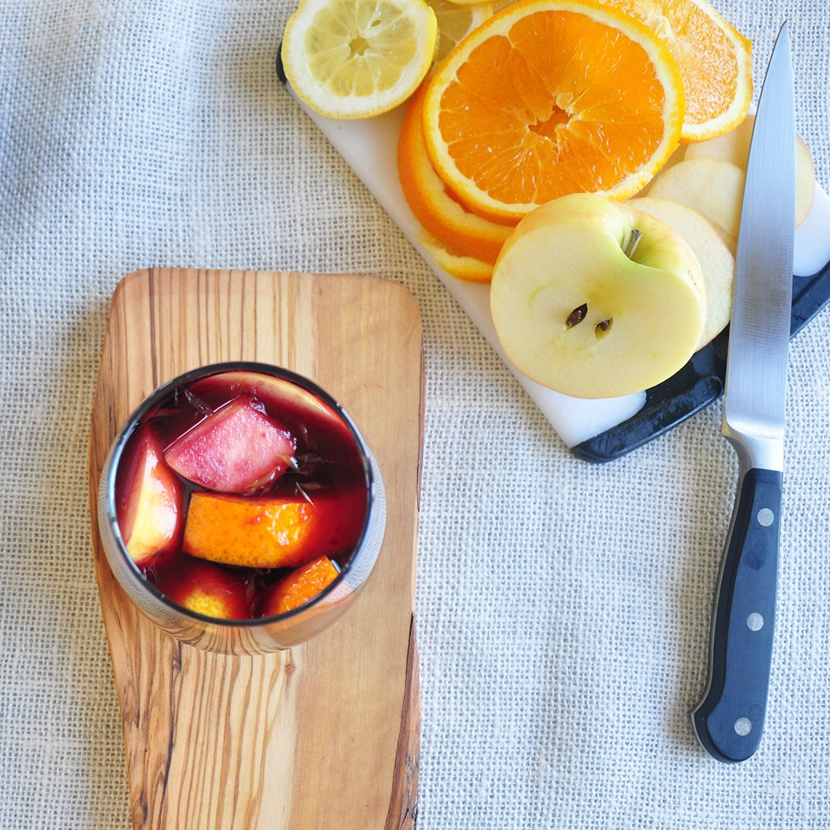 glass with sangria and fruit in it on a piece of wood. There is a cutting board with oranges, lemons and an apple on it.