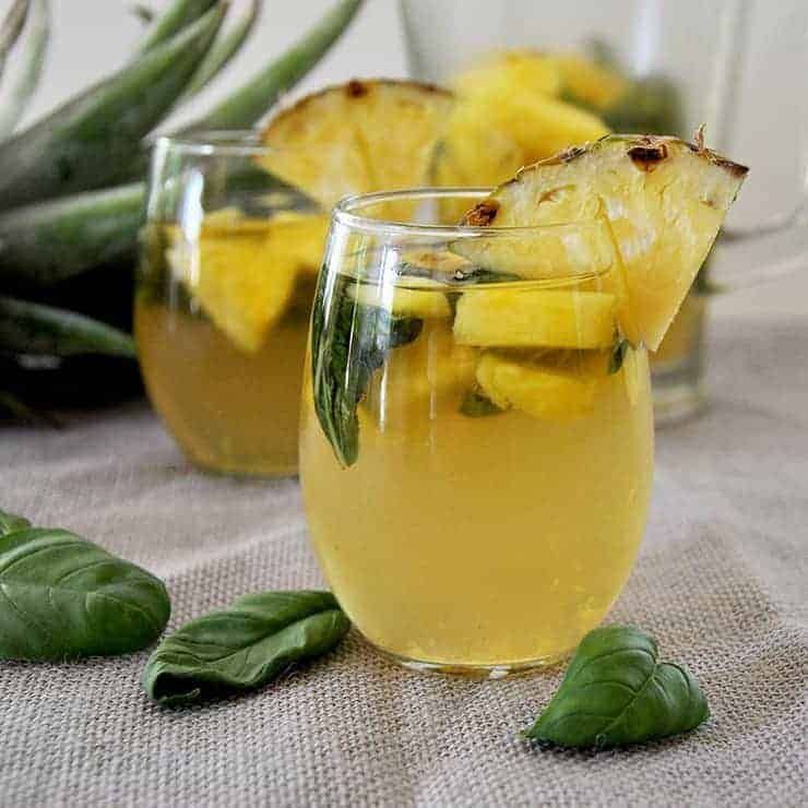 Two glasses of basil pineapple moscato sangria with some basil laying on a mat and pineapple head in the background