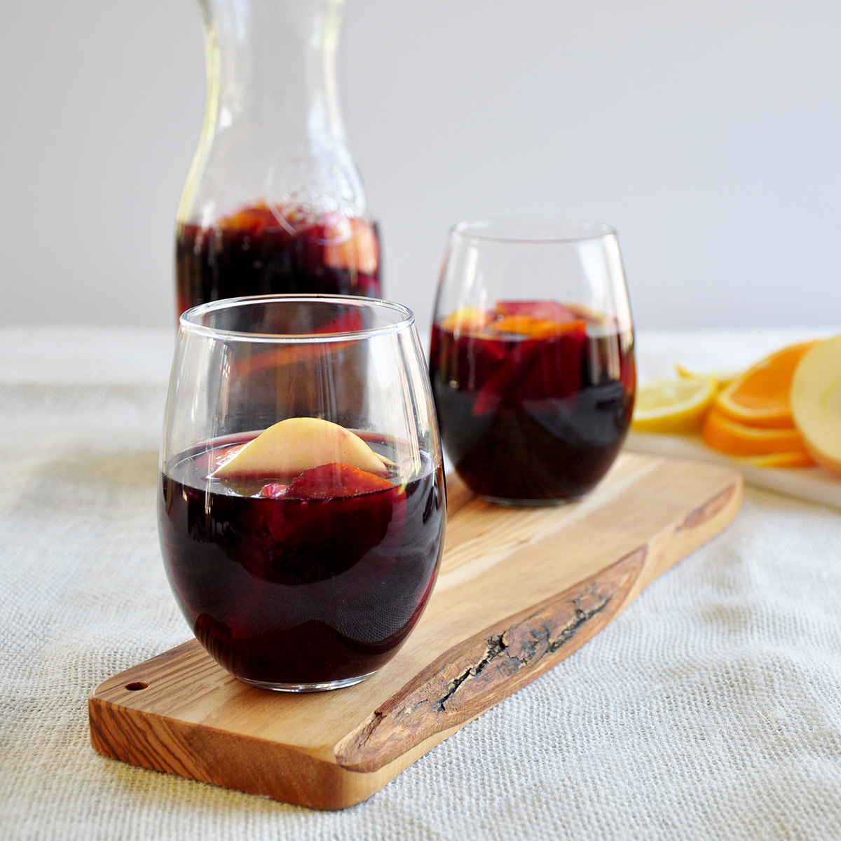 Side view of two sangrias from our easy sangria recipe with a carafe of the same in the background